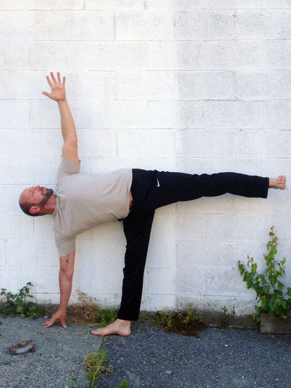 Ashok in Ardha Chandrasana against a wall