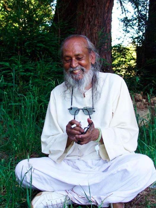 Babaji smiling, sitting under a tree